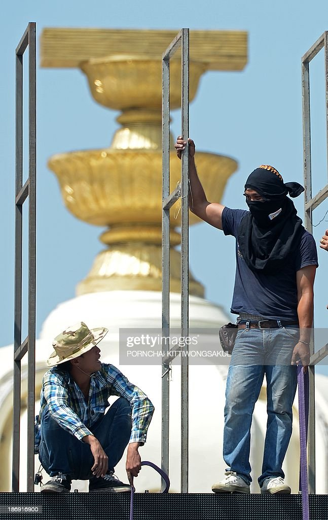 Thai opposition protesters stand on a scaffold during a rally against an amnesty bill at Democray monument in Bangkok on November 5, 2013. Thai anti-government protesters gathered in Bangkok seeking to raise pressure on the Thai government over its controversial political amnesty bill.