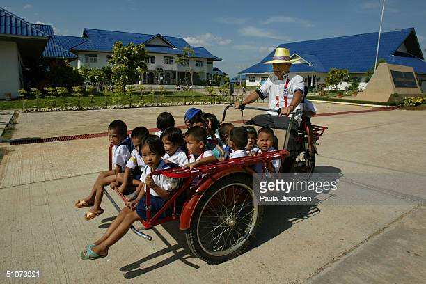 Thai orphans affected by AIDS get shuttled to their living quarters at the Wat Phrabaht Nampu AIDS orphanage funded by the Dramaraksa Foundation July...