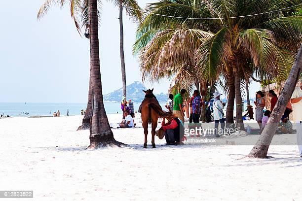Thai people between palms on beach of Hua Hin