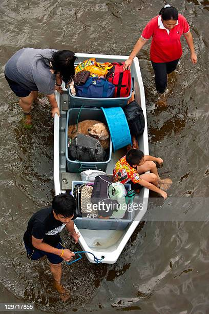Thai people carry their belongings on a boat through floodwaters in the inundated district of Rangsit northern Bangkok on October 20 2011 Thailand's...