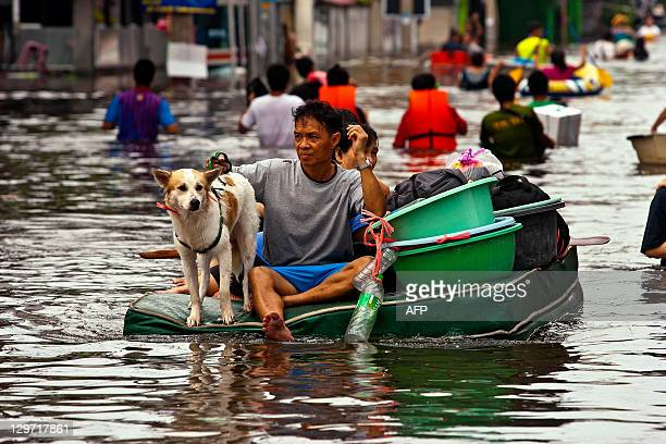 Thai people carry their belongings on a makeshift raft through floodwaters in the inundated district of Rangsit northern Bangkok on October 20 2011...