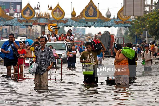 Thai people carry their belongings through floodwaters in the inundated district of Rangsit northern Bangkok on October 20 2011 Thailand's premier...