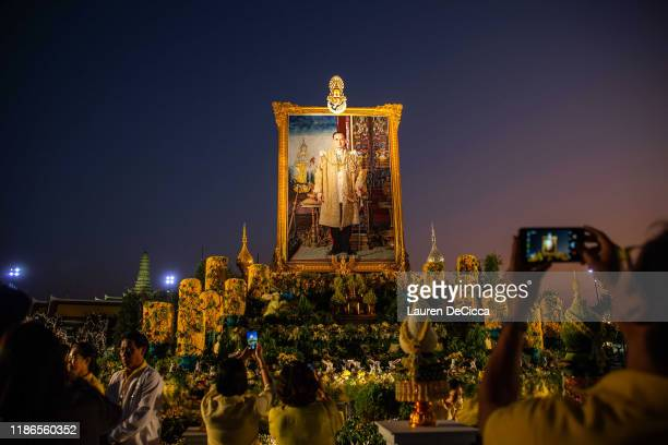Thai people gather to pray and take photos in front of a portrait of King Bhumibol at at Sanam Luang park on December 5, 2019 in Bangkok, Thailand....