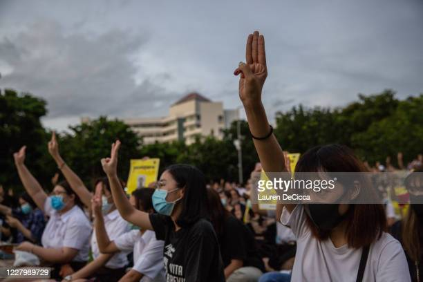 Thai people hold up a three finger salute at an anti-government protest on August 10, 2020 at Thammasat University in Bangkok, Thailand....