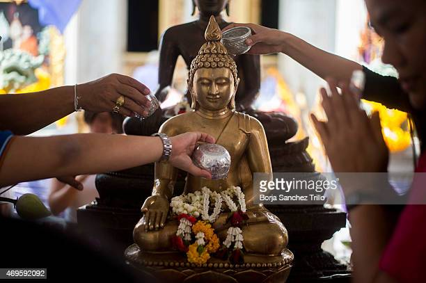 Thai people offer prayers at Wat Boworn during the Songkran water festival on April 13 2015 in Bangkok Thailand The Songkran festival marks the...
