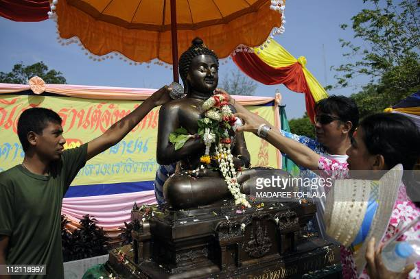 Thai people pour water on a statue of Buddha as part of celebrations of the Songkran festival marking the Thai new year in Thailand' southern...
