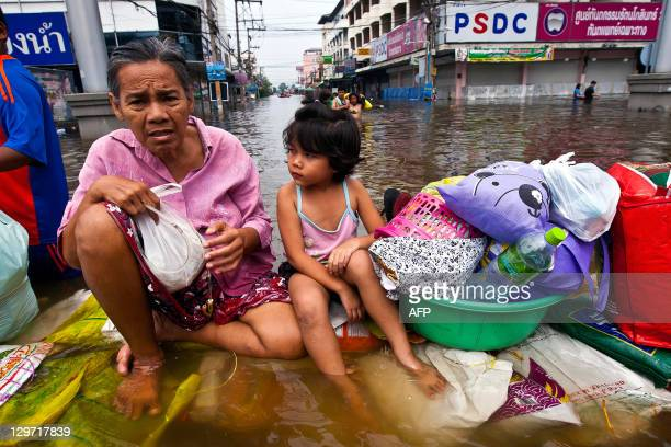 Thai people sit on a submerged sandbags barrier in the inundated district of Rangsit northern Bangkok on October 20 2011 Thailand's premier warned...