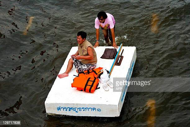 Thai people wade through floodwaters in the inundated district of Rangsit northern Bangkok on October 20 2011 Thailand's premier warned October 20...