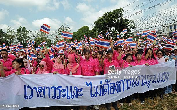 Thai people wave national flags during an antiviolence gathering in Thailand's restive southern province of Narathiwat on March 19 2016 Thailand's...