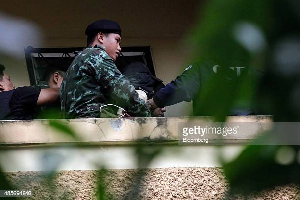Thai police and army officers escort a suspect in the August 17 Bangkok shrine bombing, center, wearing a black jacket over his head, on the balcony...