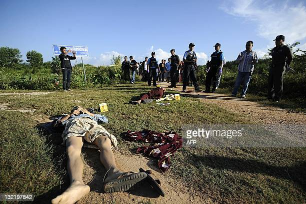 Thai police and paramilitary gather near a dead body of a Muslim villager gunned down by the suspected separatist militants in Thailand's restive...