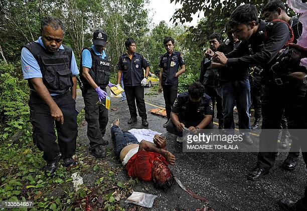 Thai police inspect the body of a villager who was shot dead by suspected separatist militants in Narathiwat province on November 20 2011 Thailand's...