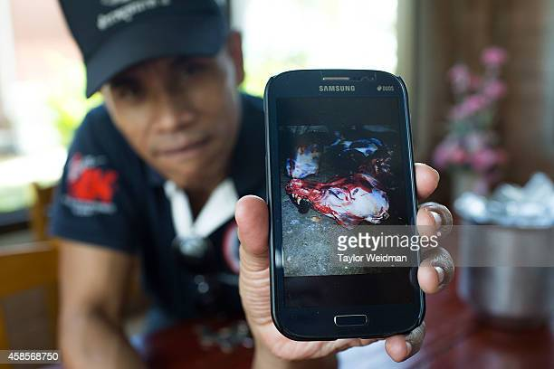 Thai police officer displays images on his mobile phone from a recent raid targetting an illegal dog slaughterhouse on November 7 2014 in Ban Tha Rae...