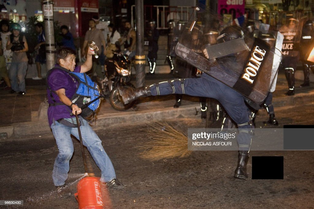 A Thai police officer (R) fights with a pro-governement protester on Silom road in the financial district of central Bangkok on April 22, 2010. One person was killed and at least 50 were injured after a series of grenade attacks rocked Thailand's protest-hit capital, officials said. AFP PHOTO / Nicolas ASFOURI