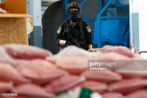 Thai police officer guards bags of methamphetamine pills during the 50th Destruction of Confiscated Narcotics ceremony to mark the International Day...