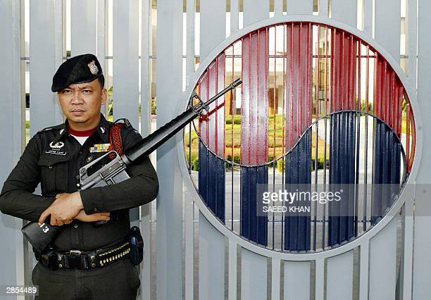 Thai police officer stands vigilant at the main enterence of the South Korean embassy in Bangkok, 09 January 2004. Thai authorities have increased...