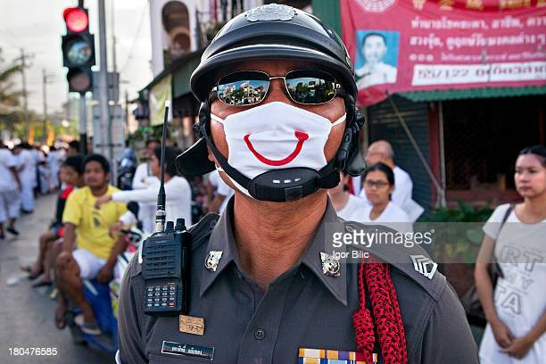 Thai police officer wearing smiley antipollution mask Many members of the Royal Thai Police wear face masks that protect them from heavily polluted...
