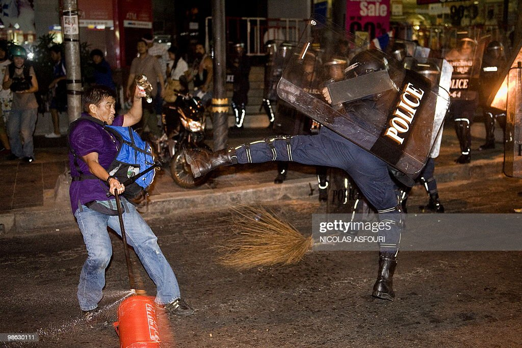 Thai police officers (R) fights with a pro-governement protester (L) on Silom road in the financial district of central Bangkok on April 22, 2010. One person was killed and at least 50 were injured after a series of grenade attacks rocked Thailand's protest-hit capital, officials said. AFP PHOTO / Nicolas ASFOURI