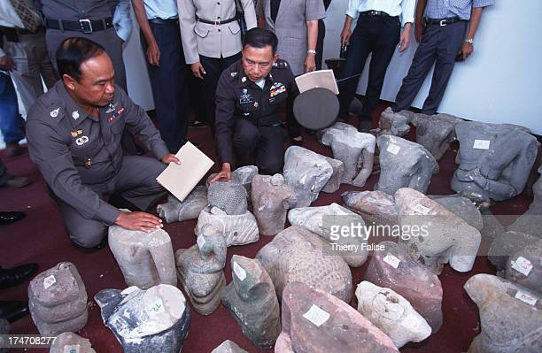 Thai police officers inspect looted Khmer antiques and other artifacts discovered on the property of an art and sculpture trafficker who is himself a...