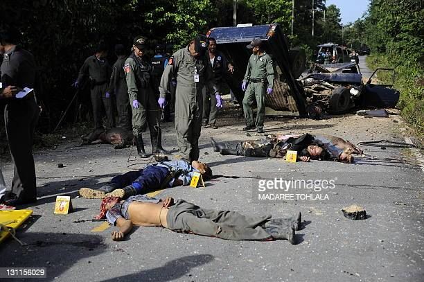 S Thai police officers inspect the bodies of six Thai buddhist huntsmen shot dead by suspected separatist Muslim militants following a roadside bomb...