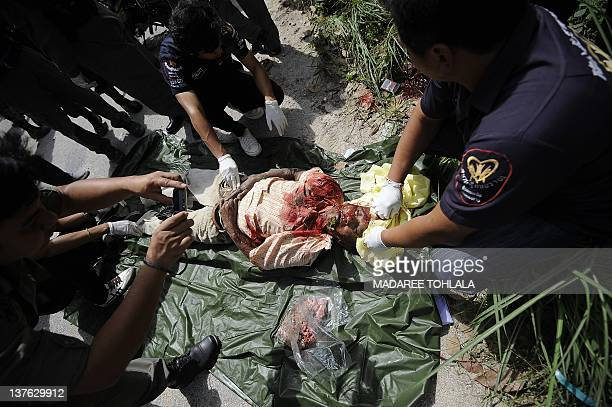 Thai police officers inspect the body of a village headman who was shot dead by suspected separatist militants in Thailand's restive southern...