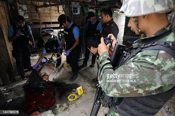 Thai police officers inspect the body of Muslim rubber dealer who was shot dead by suspected separatist militants in Thailand's southern province of...