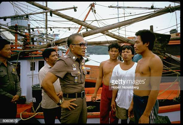 Thai police official w. Fishermen re fishermen pirates accused of criminal activities on high seas incl. Robbing & raping Vietnamese boat people.
