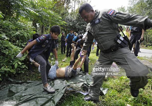 Thai police remove the body of a villager who was shot dead by suspected separatist militants from the scene of the incident in Narathiwat province...