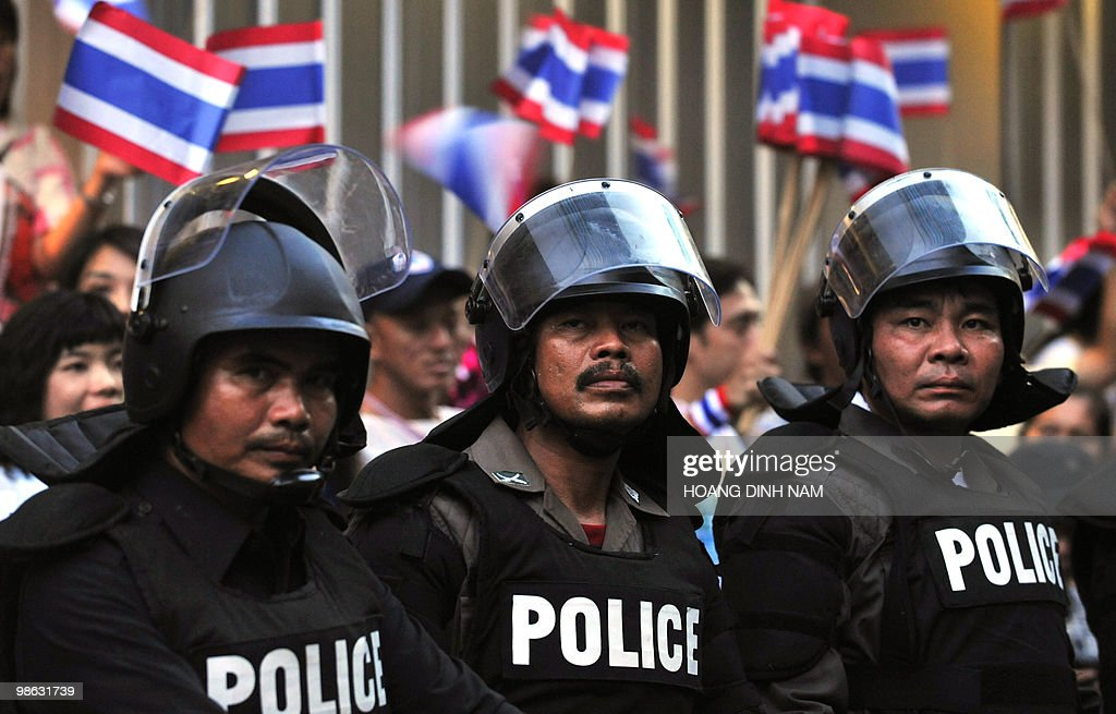 Thai police stand guard as pro-government protesters shout and wave flags behind during a rally held next to a camp of Red-Shirt anti-government protesters in the central quarter of Silom in downtown Bangkok on April 23, 2010. Thounsands of supporters of Thailand's beleaguered government rallied in Bangkok calling for an end to weeks of protests by the rival Red Shirts, following fresh bloodshed in the capital. AFP PHOTO/HOANG DINH Nam