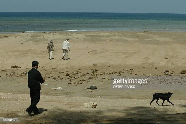 Thai policeman keeps a stray dog away as Canadian Prime Minister Paul Martin and his wife Sheila walk on Kamala beach on the tsunamistricken Thai...