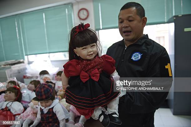 A Thai policeman shows a 'luuk thep' doll after more than a hundred of them were seized in separate raids at the Economic Crime Suppression Division...
