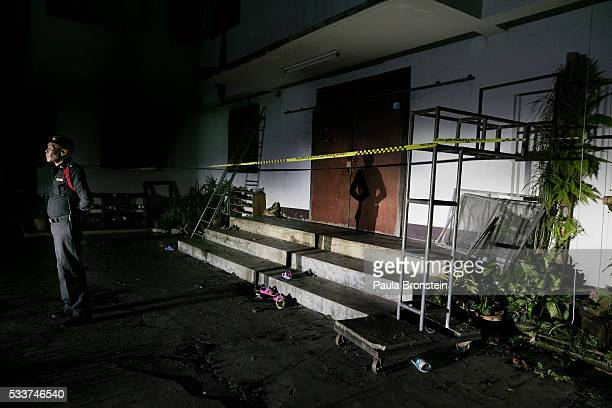 Thai policeman stands guard outside of the school dormitory where a fire broke out on Sunday night killing at least 17 girls in Wiang Papao Chiang...