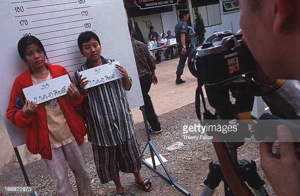Thai policeman takes identity pictures of two illegal Burmese migrants before they are repatriated to Myanmar