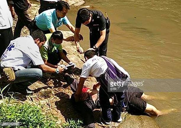 Thai policemen attend to the body of a 'mahout' who was killed by his elephant in Chiang Mai province on August 26 2015 The elephant in northern...