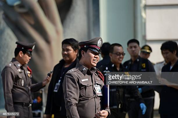 Thai policemen gather at the site of two small explosions on a walkway leading to a luxury shopping mall in Bangkok on February 2 2015 Thailand's...