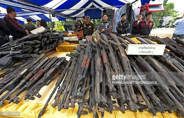 Thai policemen inspect confiscated weapons displayed prior to their destruction at Bangkok Steel Industry in Samut Prakarn province on July 15 2014...