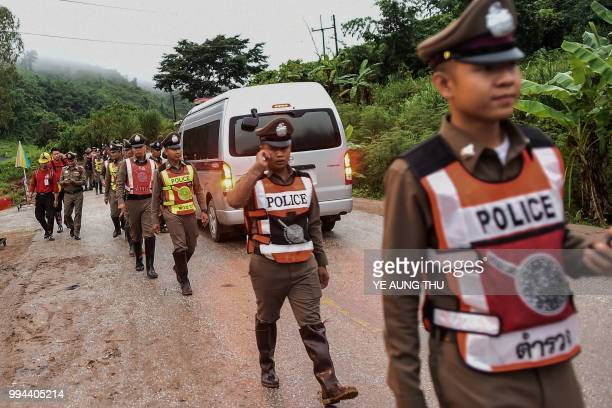 TOPSHOT Thai policemen secure the road leading to Tham Luang cave area as rescue operations continue for those still trapped inside the cave in Khun...