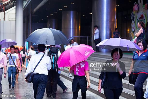 thai pople with umbrellas at rainy day in silom road - zuidoost azië stockfoto's en -beelden