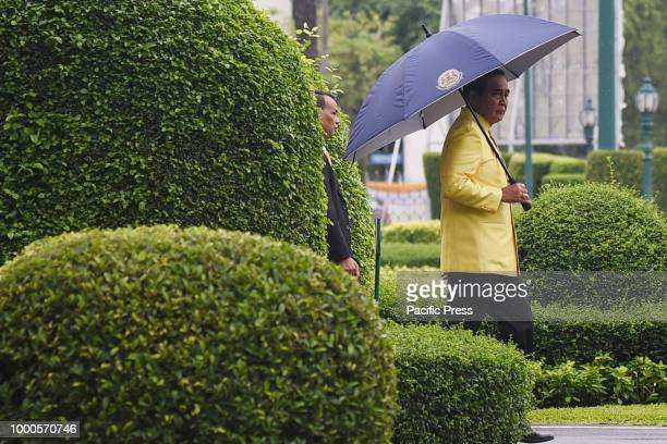 Thai Prime Minister Prayut Chanocha holding an umbrella arrives for a weekly cabinet meeting at the Government House