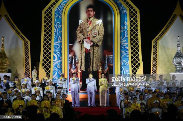 Thai Prime Minister Prayut ChanOCha raises a candle in front of a portrait of the new King of Thailand Maha Vajiralongkorn during celebrations for...