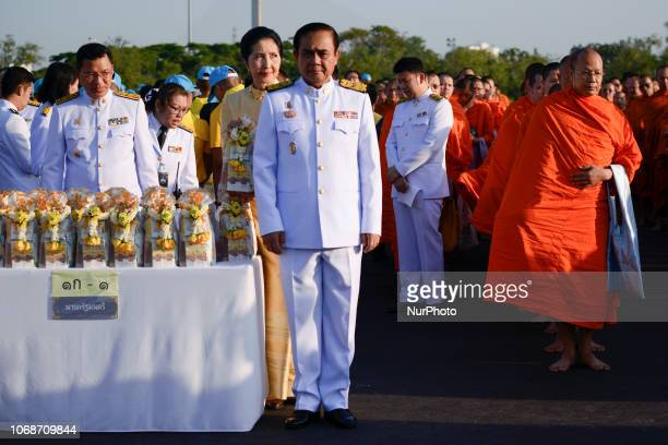 Thai Prime Minister Prayuth ChanOCha gives alms to Buddhist monks as part of in memory of late Thai King Bhumibol Adulyadej on his birthday...