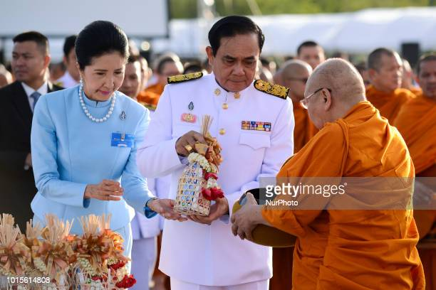 Thai Prime Minister Prayuth ChanOCha gives alms to Buddhist monks to celebrate the Queen Sirikit's 86th birthday in Bangkok Thailand 12 August 2018