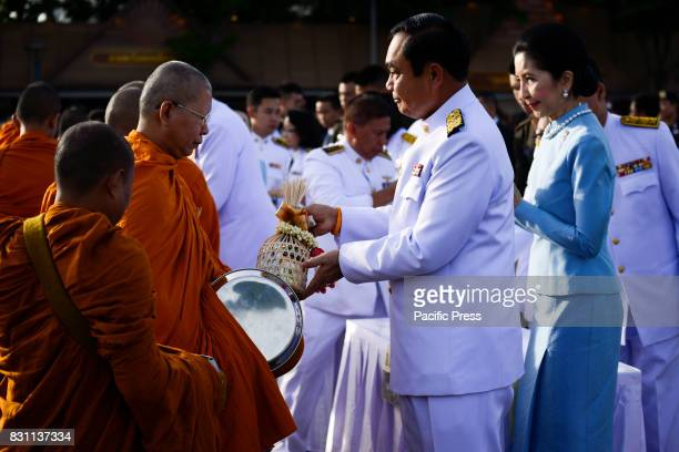 Thai Prime Minister Prayuth ChanOCha gives alms to Buddhist monks to celebrate the Queen Sirikit's 85th birthday in Bangkok Thailand 12 August 2017