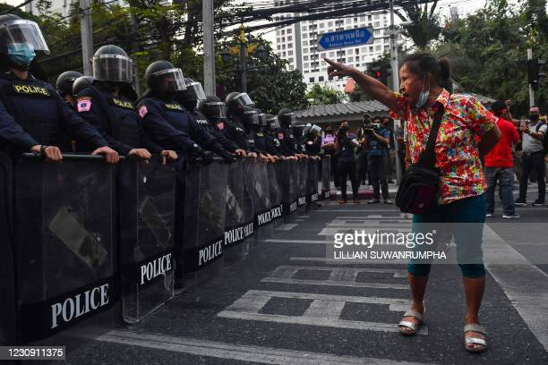 Thai pro-democracy protester gestures at riot police in Bangkok on February 1 close to where Myanmar migrants were demonstrating after Myanmar's...