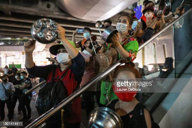 Thai pro-democracy protesters bang pots and pans during a rally at the Pathumwan Intersection on February 10, 2021 in Bangkok, Thailand. Protesters...