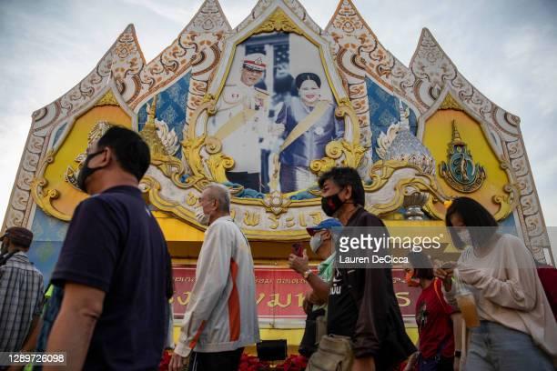 Thai pro-democracy protesters walk past a photo of King Maha Vajiralongkorn and his mother, Queen Sirikit, on December 06, 2020 in Bangkok, Thailand....