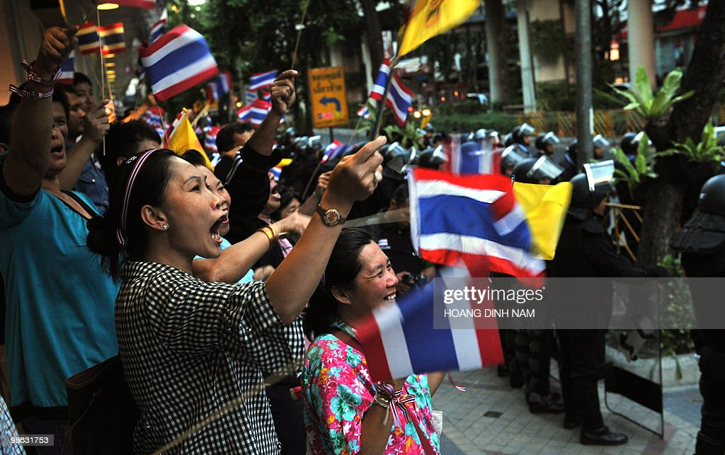 Thai pro-government protesters shout and wave national flags behind a police cordon during a rally next to a camp of Red-Shirt anti-government protesters in the central quarter of Silom in downtown Bangkok on April 23, 2010. Thousands of supporters of Thailand's beleaguered government rallied in Bangkok calling for an end to weeks of protests by the rival Red Shirts, following fresh bloodshed in the capital.