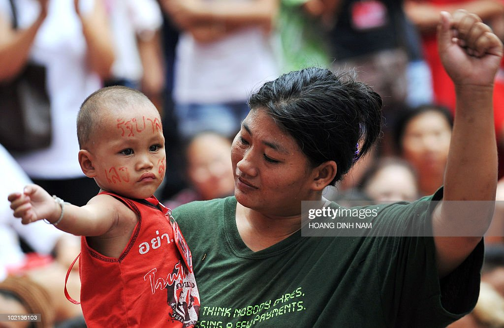 A Thai 'Red Shirt' anti-government protester teaches her son how to raise his fist prior to Red Shirts leaders' announcement they will negotiate with the government during a rally held inside their fortified camp in the Silom central financial district in downtown Bangkok on May 4, 2010. Thailand's anti-government protesters agreed on May 4, 2010 to enter the prime minister's proposed reconciliation process, raising hopes of an end to a tense political crisis that has claimed 27 lives. AFP PHOTO/HOANG DINH Nam