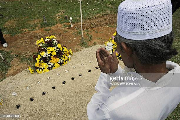 A Thai relative of a Muslim Ranger killed in an attack by suspected separatist militants in August offers prayers over his grave during his funeral...