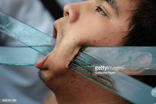 A Thai religious devotee believe to be possessed by the spirit of the god has his cheek pierced with plastic swords in order to purify himselve...